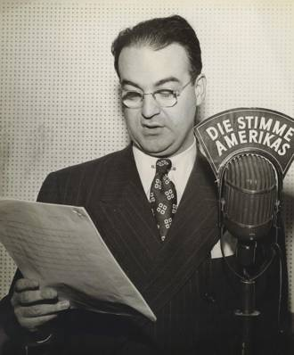 Walter Roberts speaking from behind a microphone in the early days of the Voice of America. Credit: U.S. government
