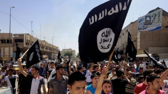 Demonstrators in support of Islamic State of Iraq and the Levant (ISIL) carry al-Qaida flags in front of the provincial government headquarters in Mosul, 225 miles (360 kilometers) northwest of Baghdad, Iraq, June 16, 2014. Source: Voice of America