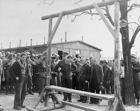 During an official tour of the newly liberated Ohrdruf concentration camp, an Austrian Jewish survivor describes to General Dwight Eisenhower and the members of his entourage the use of the gallows in the camp. Credit: National Archives and Records Administration, College Park United States Holocaust Memorial Museum, courtesy of David Wherry